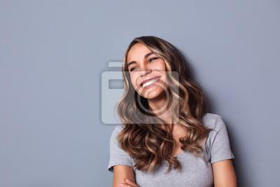 Naklejka Beautiful smiling woman studio shot on gray background.