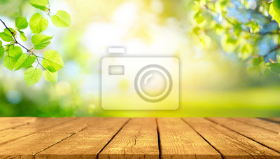 Naklejka Beautiful spring background with green juicy young foliage and empty wooden table in nature outdoor. Natural template with Beauty bokeh and sunlight.