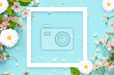 Naklejka Beautiful spring nature background with lovely blossom, petal a on turquoise blue background , top view, frame. Springtime concept.