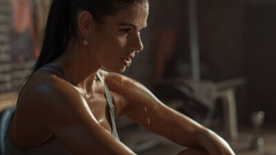 Naklejka Beautiful Strong Fit Brunette in Sport Top and Shorts in a Loft Industrial Gym with Motivational Posters. She's Catching Her Breath after Intense Fitness Training Workout. Sweat All Over Her Face.