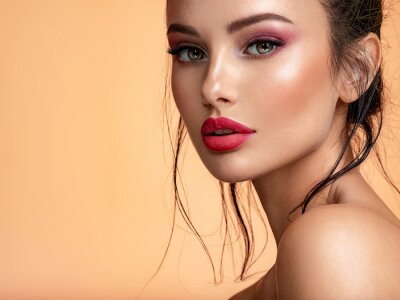 Naklejka Beautiful white girl with red lips looks to the camera. Stunning brunette girl. Closeup face of young beautiful woman with a healthy clean skin. Pretty woman with bright  makeup of eyes.