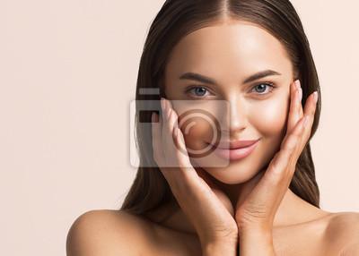 Naklejka Beautiful woman face close up natural make up hand touching face beauty smile