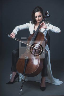 Naklejka Beautiful woman in a white coat plays the cello