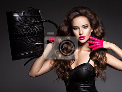 Naklejka Beautiful woman with long hair in red gloves holds black handbag