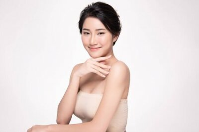 Naklejka Beautiful young Asian woman touching soft cheek and smile with clean and fresh skin. Happiness and cheerful with, isolated on white background, Beauty and Cosmetics Concept,