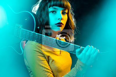 Naklejka Beautiful young hipster woman with curly hair with red guitar in neon lights. Rock musician is playing electrical guitar. 90s style concept.