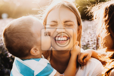 Naklejka Beautiful young mother laughing with closed eyes while her son is embracing her neck and kissing her cheek outdoor against sunset.