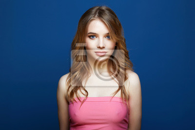 Naklejka Beautiful young woman in pink dress over blue background