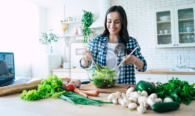 Naklejka Beautiful young woman is preparing vegetable salad in the kitchen. Healthy Food. Vegan Salad. Diet. Dieting Concept. Healthy Lifestyle. Cooking At Home. Prepare Food. Cutting ingredients on table