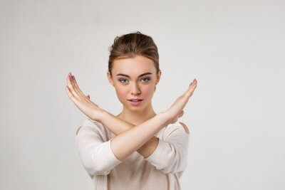 Naklejka beautiful young woman making stop gesture on gray background.
