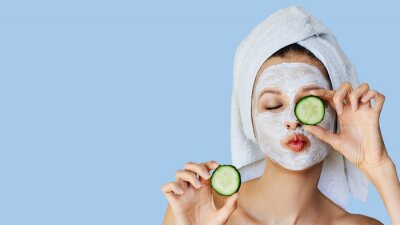 Naklejka Beautiful young woman with facial mask on her face holding slices of cucumber. Skin care and treatment, spa, natural beauty and cosmetology concept.
