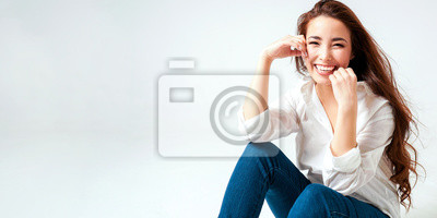 Naklejka Beauty fashion portrait of smiling sensual asian young woman with dark long hair in white shirt on white background banner