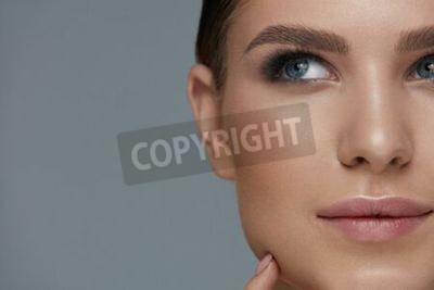 Naklejka Beauty makeup. Woman face with beautiful eyes and eyebrows make-up and long black eyelashes closeup