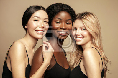 Naklejka Beauty. Multi Ethnic Group of Womans with diffrent types of skin  together and looking on camera. Diverse ethnicity women - Caucasian, African and Asian posing and smiling against beige background.