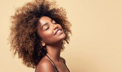 Naklejka Beauty portrait of african american girl with clean healthy skin on beige background. Smiling dreamy beautiful black woman.Curly  hair in afro style