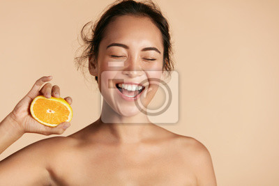 Naklejka Beauty. Smiling woman with radiant face skin and orange portrait. Beautiful smiling asian girl model with natural makeup, healthy smile and glowing hydrated facial skin. Vitamin C cosmetics concept