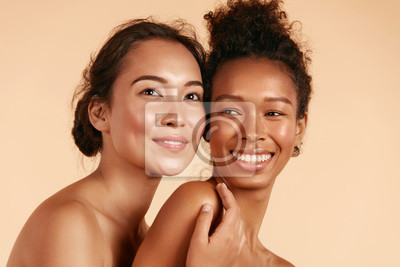 Naklejka Beauty. Smiling women with perfect face skin and natural makeup portrait. Beautiful happy asian and african girl models with different types of skin on beige background. Spa skin care concept