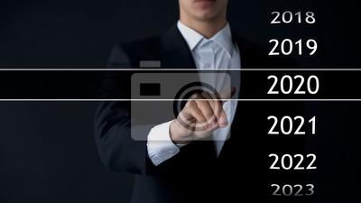 Naklejka Biznesmen wybiera 2020 rok w wirtualnym menu, wyszukiwaniu danych, historii biznesu