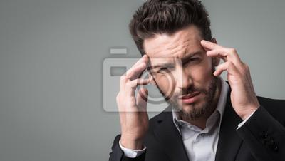 Biznesmen z bólem głowy głową w dłoniach
