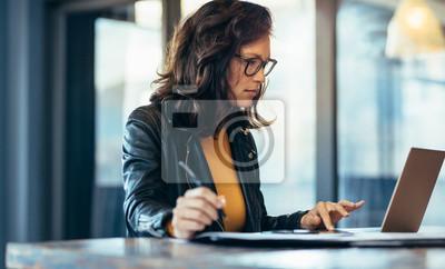 Naklejka Bizneswoman robi notatkom patrzeje laptop