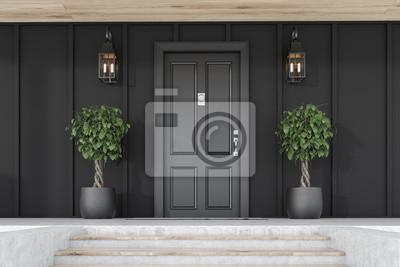 Naklejka Black front door of black house with trees