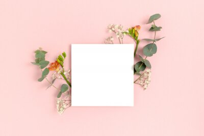 Naklejka Blank paper card mockup with frame made of flowers and eucalyptus. Floral composition with copy space on a pink pastel background.
