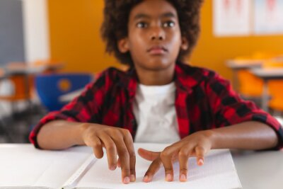 Naklejka Blind african american schoolboy sitting at desk in classroom reading braille book with fingers