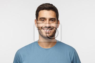 Naklejka Bliska portret młody uśmiechnięty przystojny facet w niebieską koszulkę na białym tle na szarym tle
