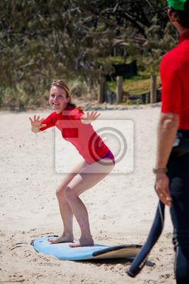 Naklejka Blond dziewczyna nauka surfowania na plaży