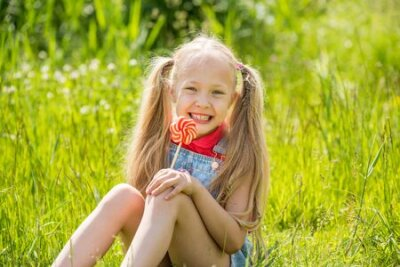 Naklejka Blonde little girl with long hair and candy on a stick
