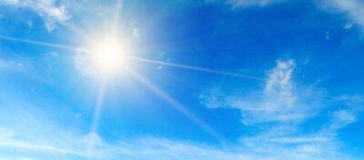 Naklejka Blue sky. Bright midday sun illuminates the space. Wide photo .