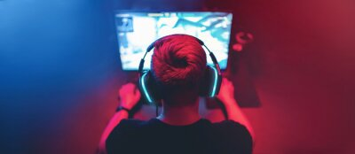 Naklejka Blurred background professional gamer playing tournaments online games computer with headphones, red and blue