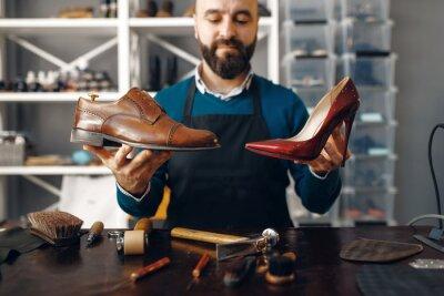 Naklejka Bootmaker shows repaired shoes, footwear repair