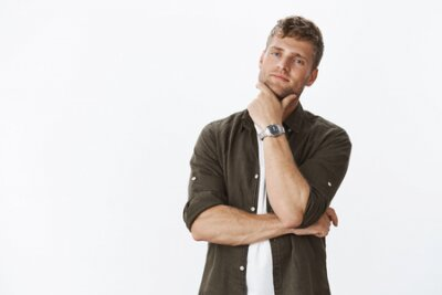 Naklejka Bossy good-looking smart and confident attractive blond businessman with bristle and watch touching jaw looking determined and curious at camera, thinking, making choice as intrigued with product