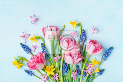 Naklejka Bouquet of beautiful spring flowers on pastel blue table top view. Greeting card for International Women Day. Flat lay.