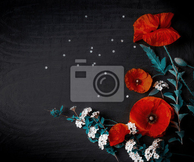 Bouquet of red poppies and white Spiraea on a black background. Wild flowers.
