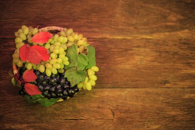 bowl with grapes, and autumn leaves on an old wooden background