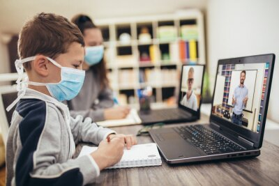 Naklejka Boy and girl studies at home, wear protective masks, and doing school homework. Distance learning online education.