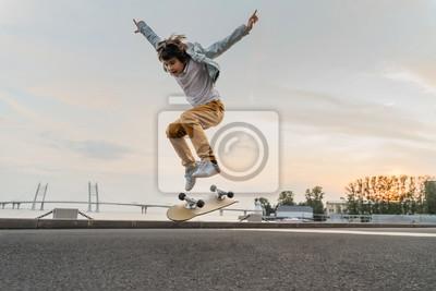 Naklejka Boy jumping on skateboard at the street. Funny kid skater practicing ollie on skateboard at sunset.
