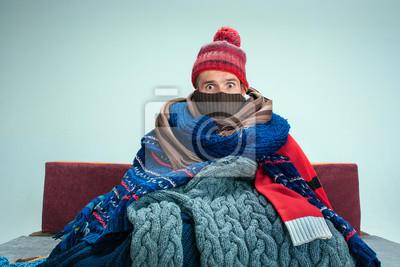 Naklejka Brodaty chory człowiek z kominkiem siedzi na kanapie w domu lub studio pokryte dzianiny ciepłe ubrania. Choroba, grypa, koncepcja bólu. Relaks w domu. Koncepcje opieki zdrowotnej.