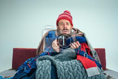 Naklejka Brodaty chory człowiek z kominkiem siedzi na kanapie w domu lub studio z filiżanką herbaty pokryte dzianiny ciepłe ubrania. Choroba, koncepcja grypy. Relaks w domu. Koncepcje opieki zdrowotnej.