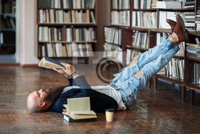 Naklejka Brodaty mężczyzna hipster relaks i czytanie książki leży na podłodze