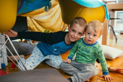 Naklejka brothers playing in their built indoor fort in living room