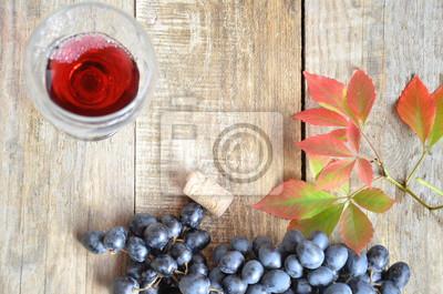 Brush czarne winogrona na drewnianej powierzchni, kopia przestrzeń. czerwone wino i winogrona. Wino i winogrona w zabytkowe ustawienie z korka na drewnianym stole. z czerwonymi liśćmi. koncepcja jesie