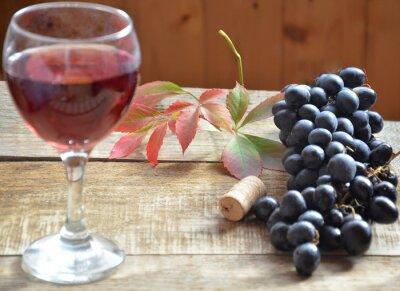 Brush czarne winogrona na drewnianej powierzchni, kopia przestrzeń. Wino i winogrona w zabytkowe ustawienie z korka na drewnianym stole. koncepcja jesieni