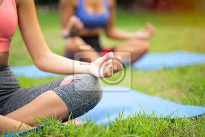 Naklejka Buddy woman training asana yoga by doing lotus pose for meditation, balance body at outdoor park with trainer. Control their mind to peace and concentrate a meditating, outside fitness among natural