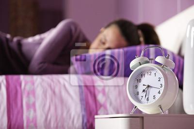Budzik z śpi młoda kobieta w tle
