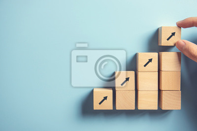 Naklejka Business concept growth success process, Close up Woman hand arranging wood block stacking as step stair on paper blue background, copy space.