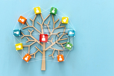 Naklejka Business image of wooden tree with people icons over blue table, human resources and management concept