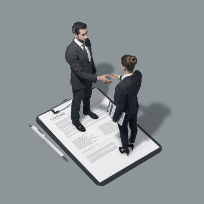Business people signing a contract and shaking hands